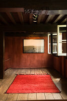 Picture on wall and red rug in simply decorated, renovated Antwerp house