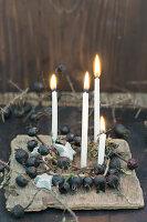 Kranz aus schwarzen Hagebutten mit vier Kerzen und Sternen aus Birkenrinde