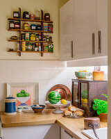 Sauces and spices on wooden, wall-mounted shelves in corner of kitchen