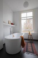 Frei stehende Badewanne im Badezimmer mit Fenster