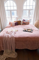 Scatter cushions, bedspread and tray on double bed in front of arched bedroom windows