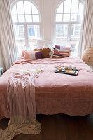 Doppelbett mit Kissen, Tagesdecke und Tablett vor Rundbogenfenstern im Schlafzimmer