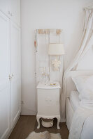 Lamp mounted on old window shutters on wall above vintage-style bedside table