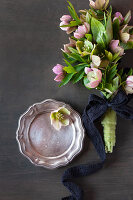 Bouquet of hellebores tied with dark ribbon and pewter plate on dark surface