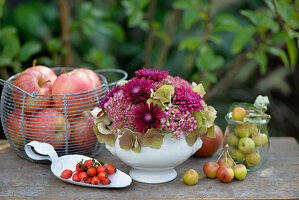 Gesteck aus Hortensien, Fetthenne und Chrysanthemen, daneben Äpfel und Zieräpfel