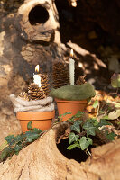 Terracotta plant pots decorated for autumn with felt and pine cones and used as candle holders
