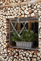 Star made of branches covered in lichen in front of window surrounded with stacked firewood