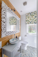 Mirror with elaborate frame above sink