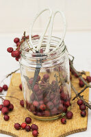 Haws and scissors in jam jar on wooden board