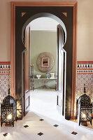 Türrahmen, flankiert von Bodenlaternen, Blick auf Konsolentisch und Wandspiegel