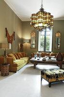 Sofagarnitur mit Kissen in Lounge mit grünen Wänden