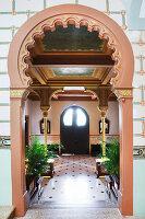Blick durch kunstvollen Rundbogen in Eingangshalle mit Deckenfresko