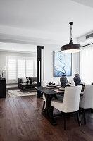 Dunkler Tisch mit gepolsterten Stühlen im Esszimmer mit dunklem Dielenboden