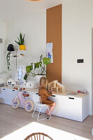 Child sitting at sideboard playing with dolls' house in front of strip of cork pinboard on wall