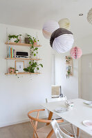 Lanterns and honeycomb balls above dining table and next to wall-mounted shelves