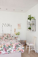Floral bed linen on bed in white bedroom
