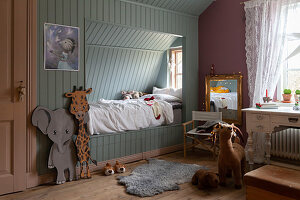 Pale blue cubby bed in child's bedroom with pink walls and vintage desk