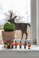 Festive arrangement of potted succulent, reindeer and gnome musicians on windowsill