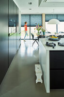 Black cupboards and white high-gloss breakfast bar in open-plan kitchen