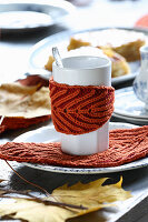 Hand-knitted mug warmers and leaf-shaped coasters for decorating autumnal table