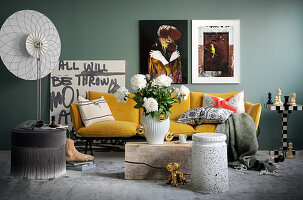 Artworks and yellow sofa against grey wall in living room
