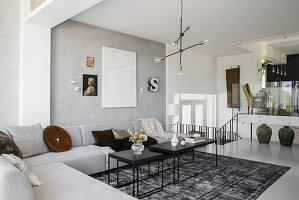 Corner sofa in pale grey designer living area with dining area in background on raised level