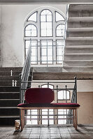 Bench with claret-red upholstery in stairwell with arched window