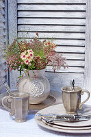 Jug of wild carrot 'Dara' flowers, place setting with mugs and silver cutlery