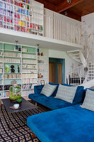 Blue velvet modular sofa in maisonette apartment with white winding staircase and gallery