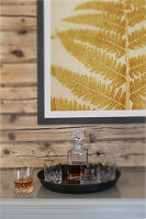 Carafe and whisky glasses on tray below picture of fern leaf