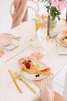 Waffeln mit Früchten auf festlich gedecktem Tisch in zarten Rosatönen