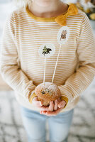Child holding muffin with decorative skewers