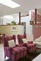 Pink striped armchairs in open-plan, split-level interior