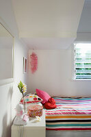 Light-flooded, white bedroom with colourful bed linen