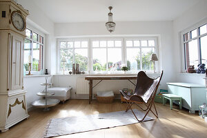 Designer easy chair in rustic room with window bay