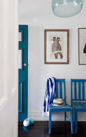 Blue-and-white striped scarf hanging on backrest of blue chair in hall