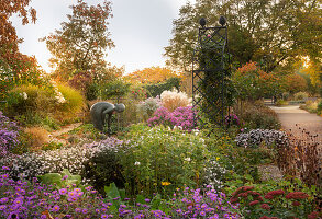 Bronze sculpture in flowering garden (district teaching garden, Steinfurt, Germany)