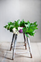 Kranz aus Fliedern und Maiglöckchenblättern auf Hocker