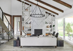 Living room with wood beams and trim, large glass sliding doors to outside, marble clad fireplace