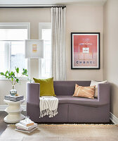 Sitting area with purple modern sofa, print, white side table topped with striped box and leaves in a glass vase
