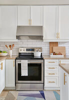 White kitchen with light wood accents, stainless appliances, brass hardware and white subway tiles