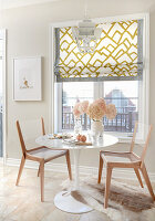Breakfast nook in kitchen with abstract graphic art work, and mustard yellow graphic roman blind, white colonial pendant