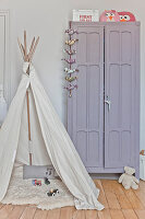 Play wigwam with sheepskin rug in front of lilac wardrobe