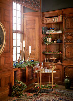 Drinks trolley in front of festively decorated wooden shelves and windowsill