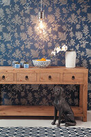 Holzkonsole mit Schubladen, Glühbirne und Hundeskulptur vor blauer Tapete mit Blättermotiv