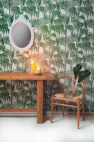 Holztisch und Klassikerstuhl vor Tapete mit Pflanzenmotiv