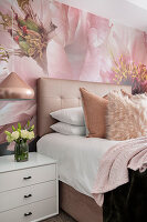 Double bed with button-tufted headboard, bedside cabinet below pendant lamp and wallpaper with huge floral motif in bedroom