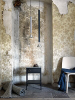 Rolled rug, side table, pendant lamps and chair in room with peeling wallpaper