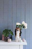 Vasensammlung und Hundefigur vor blaugrauer Bretterwand