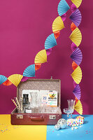 Colourful garland of paper fans above open suitcase used as drinks tray